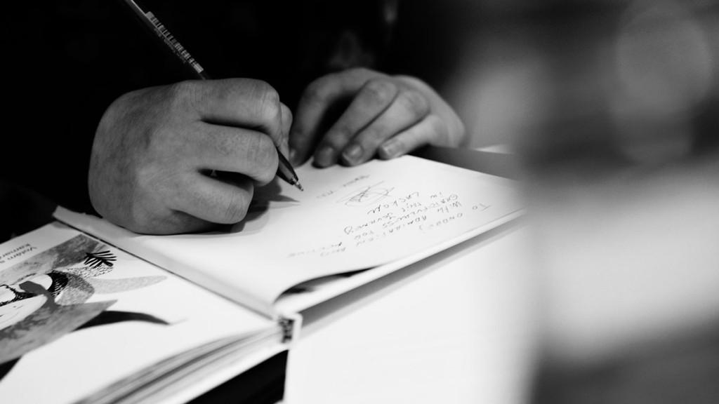 """Iván Gómez firmando copias de su libro infantil """"Las aventuras de Ayu y Grof: En tierra de volcanes"""" sobre la pérdida con ilustraciones de Mirari Sagarzazu"""